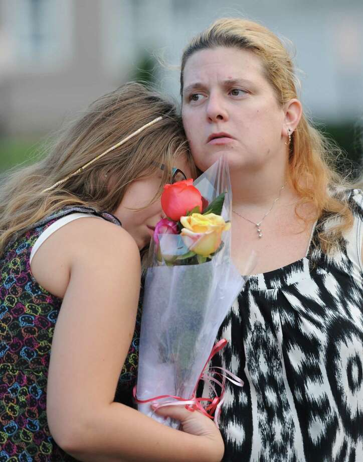 Robyn Higley,11, cries on the shoulder of her mother Vycki Pratt, at the September 11th remembrance ceremony at Elmwood Park in Danbury, Conn. on Wednesday, Sept. 11, 2013.  Robert Higley, father of Robyn and husband of Vycki, died in the terrorist attacks 12 years ago.  Danbury Mayor Mark Boughton led the ceremony, remembering those who lost their lives. Photo: Tyler Sizemore / The News-Times