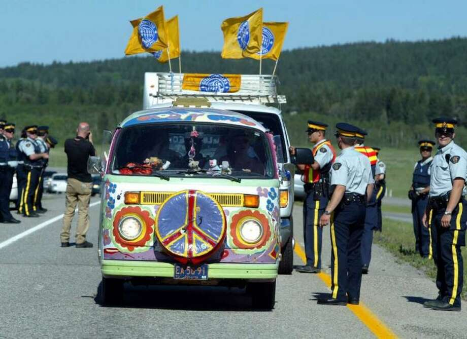 Royal Canadian Mounted Police allow a protester's vehicle past the first police checkpoint near where Group of Eight leaders met June 26, 2002 in Kananaskis, Alberta, Canada. Approximately 300 protesters were attempting to gain access to the highly secure site where the world leaders are meeting. Photo: Jeff Vinnick, Getty Images