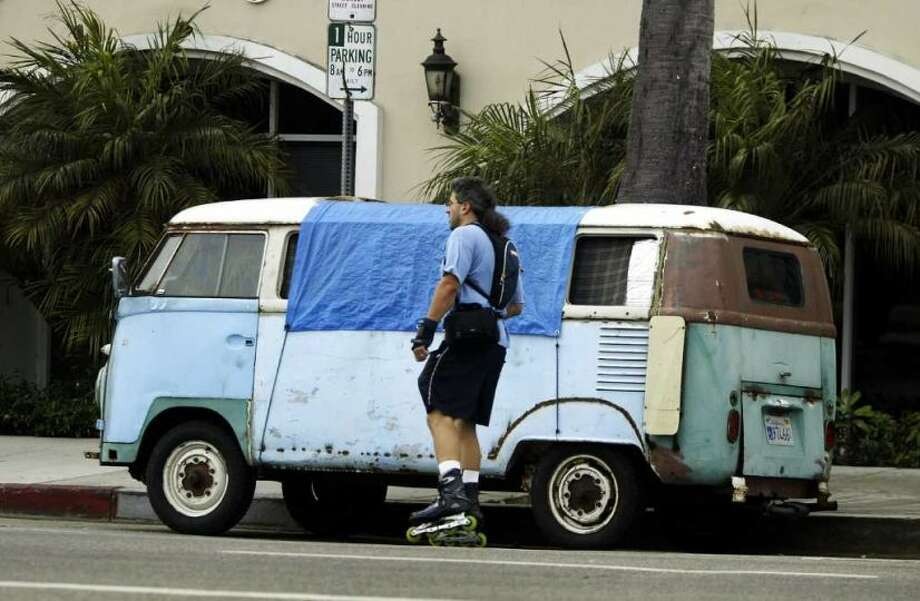 A skater passes a van where a homeless person is sleeping July 13, 2004 in Venice, California. An influx of wealthy home buyers drove real estate prices up, and affordable housing for local residents out. Photo: David Mcnew, Getty Images