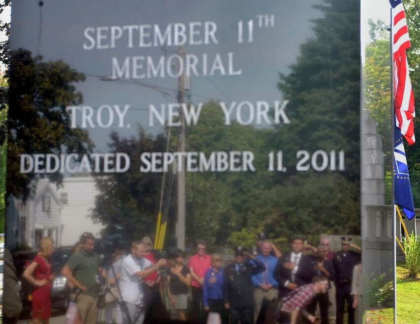 Those attending a service at the September 11th Memorial are seen reflected in it Wednesday afternoon, Sept. 11, 2013, in Troy, N.Y. A wreath was laid at the memorial by Troy Mayor Lou Rosamilia and Jim Gordon, who was the chairman of the coordinating committee for the memorial. (Paul Buckowski / Times Union)