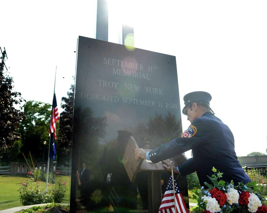 Retired New York City firefighter Bill Messina of Latham reaches down to touch a piece of steel from the World Trade Center site Wednesday, Sept. 11, 2013, in Troy, N.Y.  Messian was retired when the attacks happened but some of the fellow firefighters he had worked with in the city lost their sons who were also firefighters.  A wreath was laid at the memorial by Troy Mayor  Lou Rosamilia and Jim Gordon, who was the chairman of the coordinating committee for the memorial.    (Paul Buckowski / Times Union) Photo: Paul Buckowski / 00023800A