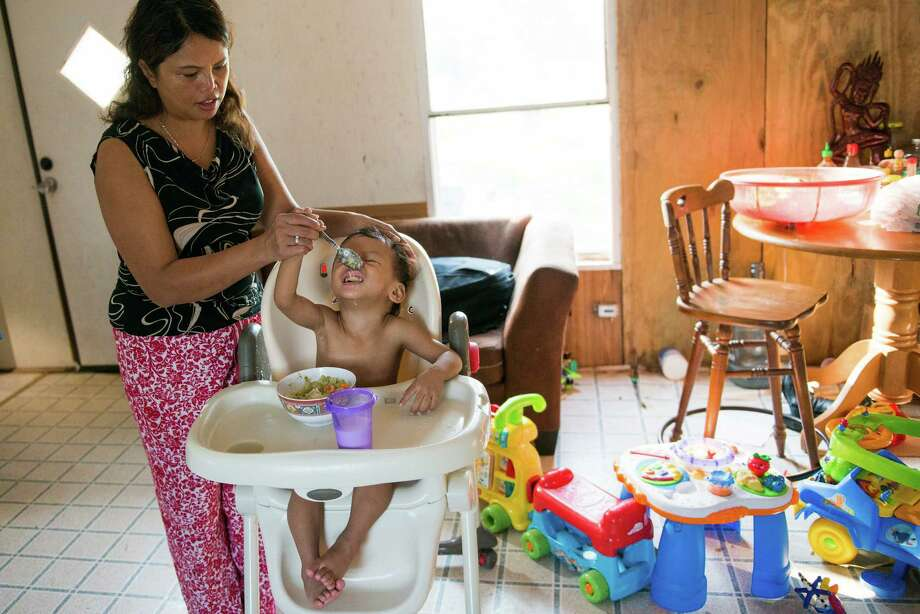Farmer Phalanie Sar feeds her 2-year-old Somnang - the Khmer word for Lucky. A community of Cambodian farmers moved to the area after fleeing violence in their homeland. Photo: Smiley N. Pool, Houston Chronicle / © 2013  Houston Chronicle