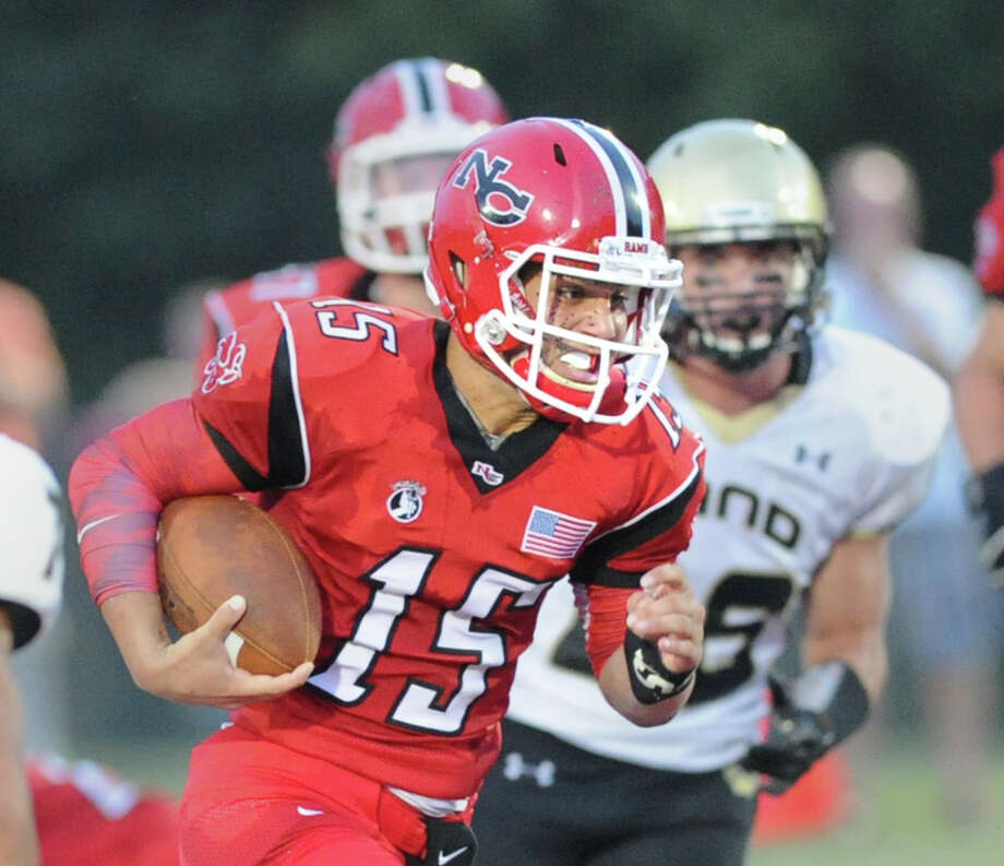 At left, New Canaan quarterback Nick Cascione, # 15, runs the ball during football game between New Canaan High School and Daniel Hand High School, at New Canaan, Wednesday, Sept. 11, 2013. Photo: Bob Luckey / Greenwich Time