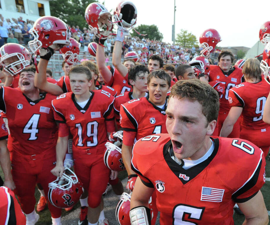 At right, Teddy Bossidy, # 6 of New Canaan, leads a pre-game cheer before the start of the football game between New Canaan High School and Daniel Hand High School, at New Canaan, Wednesday, Sept. 11, 2013. At left are teammates, Frank Cognetta, #4, and Liam Harris, # 19. Photo: Bob Luckey / Greenwich Time