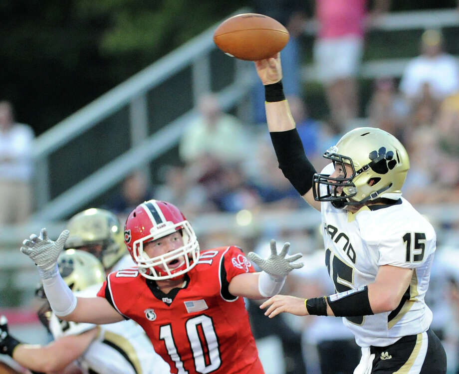 At left, Alex Dobbin, # 10 of New Canaan, pressures Daniel Hand quarterback, Hayden Atwater, # 15, during football game between New Canaan High School and Daniel Hand High School, at New Canaan, Wednesday, Sept. 11, 2013. Photo: Bob Luckey / Greenwich Time