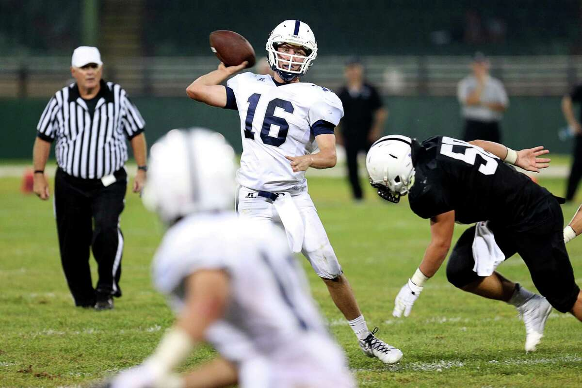 Mike Ross Connecticut Post freelance -Staples High School's quarterback # 16 Jack Massie eyes an open teammate down field while escaping the rush from Xavier High School's defense during Wednesday evening Class LL heavyweights season opener.
