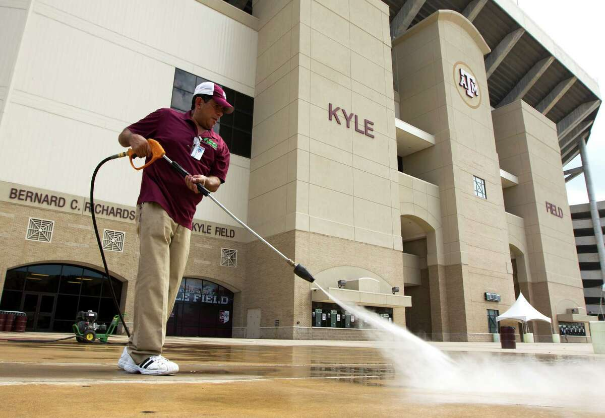 Heraclio Lopez cleans the sidewalks around Kyle Field on Texas A&M University campus on Wednesday, Sept. 11, 2013, in College Station in preparation for the A&M / Alabama football game.