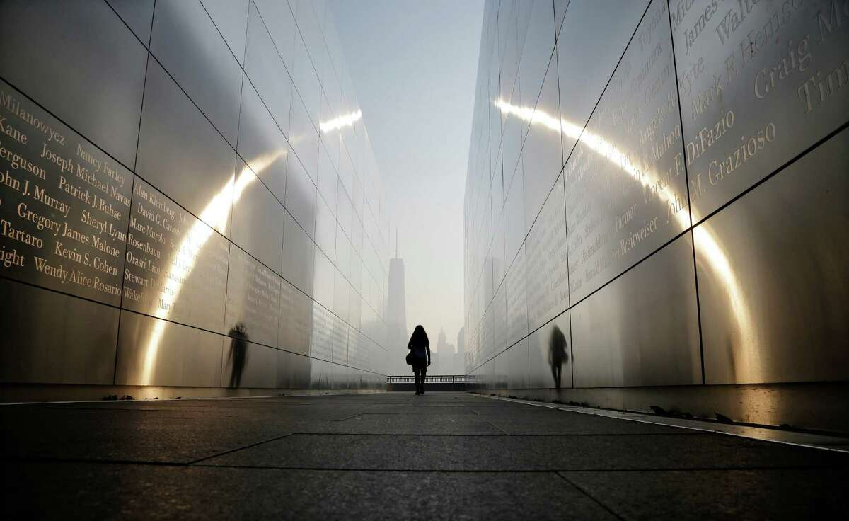 """A visitor walks through the """"Empty Sky"""" memorial to New Jersey's victims of the Sept. 11, 2001 terrorist attacks on Wednesday, Sept. 11, 2013, in Jersey City, N.J. One World Trade Center is visible across the Hudson River. Ceremonies will be held Wednesday to mark the 12th anniversary of the attacks."""