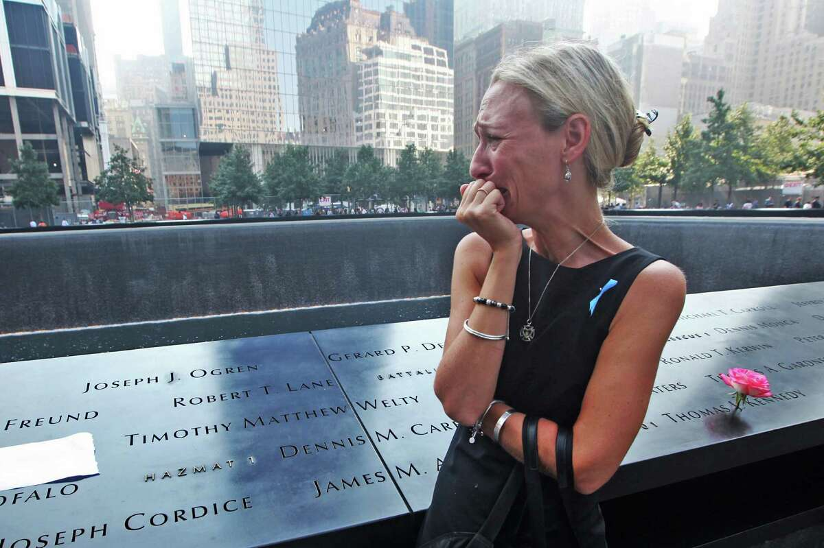 Carrie Bergonia of Pennsylvania looks over the name of her fiance, firefighter Joseph Ogren, at the 9/11 Memorial during ceremonies marking the 12th anniversary of the 9/11 attacks on the World Trade Center in New York, Wednesday, Sept 11, 2013.