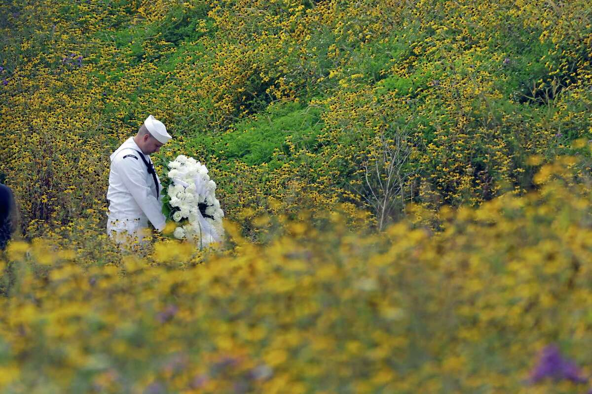 Navy Quartermaster Matthew Konchan of Johnstown, Pa., stands in a field of black-eyed Susan as he waits to participate in a wreath laying with Secretary of the Interior Sally Jewell during a memorial service at the Flight 93 National Memorial on Wednesday, Sept. 11, 2013 in Shanksville.