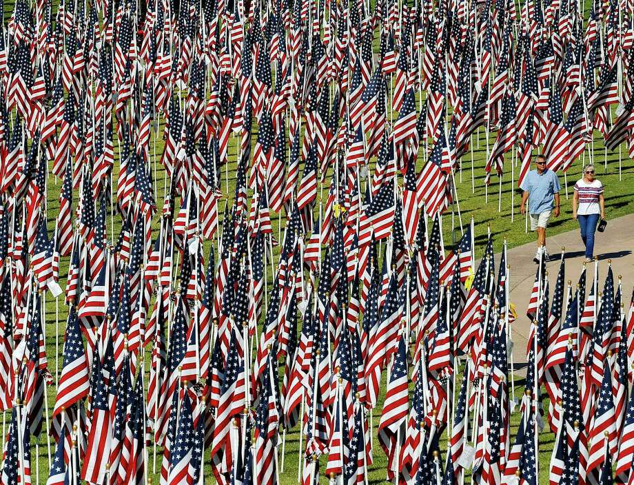 "A couple walks through the ""Healing Field"" at Tempe Beach Park, Wednesday, Sept. 11, 2013, in Tempe, Ariz. on the 12th anniversary of the 9/11 terrorist attacks. The display has nearly 3,000 flags with the names of those who died in the 2001 attacks. Photo: Matt York, Associated Press / AP"