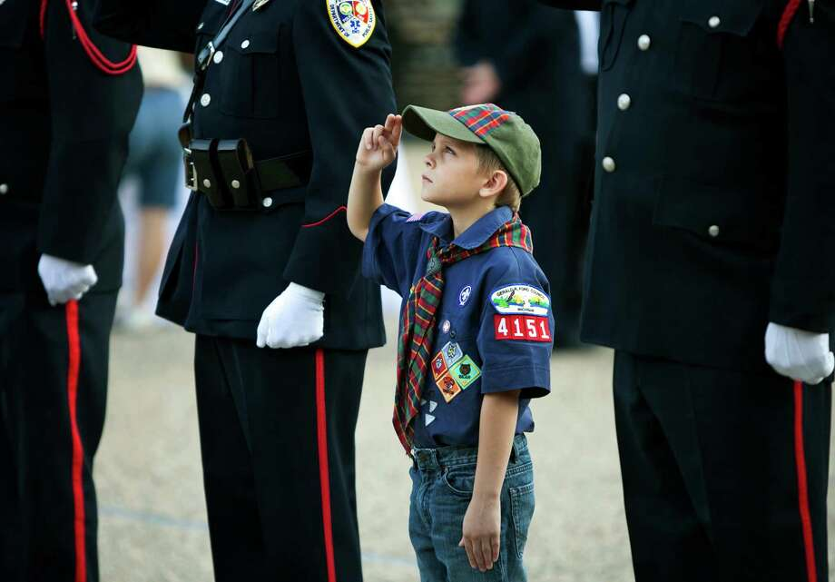 Cub Scout Nicholas Rea salutes the flag with police and firefighters during a ceremony on the 12th anniversary of the 9/11 terrorists attacks Wednesday, Sept. 11, 2013, at the Gerald R. Ford Presidential Museum in Grand Rapids, Mich. Photo: Cory Morse, Associated Press / The Grand Rapids Press