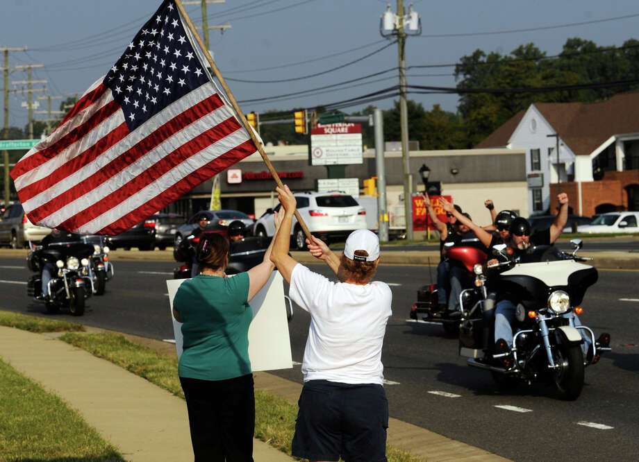 "Pat Brown waves United States flag as motorcyclists leave the Brafferton Shopping Center in Stafford, Va. on Wednesday, Sept. 11, 2013, for the ""2 Million Bikers to DC"" event to commemorate the 12th anniversary of the 9/11 terrorist attacks. Photo: Peter Cihelka, Associated Press / The Free Lance-Star"