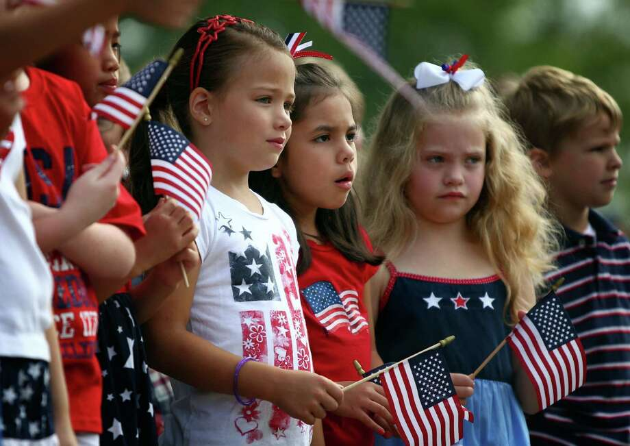Fom left, Altruria Elementary students Kate Switzer, Gaby Aguilar, Gracie David, and John Sanders participate in the school's annual Altruria Elementary School Remembers ceremony in honor of 9/11 terrorist attacks in Bartlett, Tenn. Wednesday, Sept. 11, 2013. The students gathered for a moment of silence, a flag presentation, the Pledge of Allegiance and National Anthem. Photo: Nikki Boertman, Associated Press / The Commercial Appeal