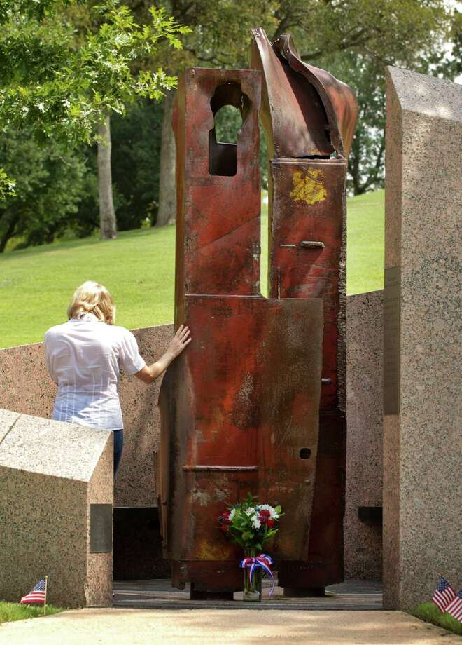 Karen Sironi pays her respects to those killed in the Sept. 11, 2001, terrorist attacks, at the 9/11 Monument at the Texas State Cemetery in Austin, Texas, on Wednesday, Sept. 11, 2013. The monument includes steel columns that were salvaged from the World Trade Center. Sironi said the attacks hit her hard because she was a ticket agent for American Airlines at the time of the attacks. Photo: Jay Janner, Associated Press / Austin American-Statesman