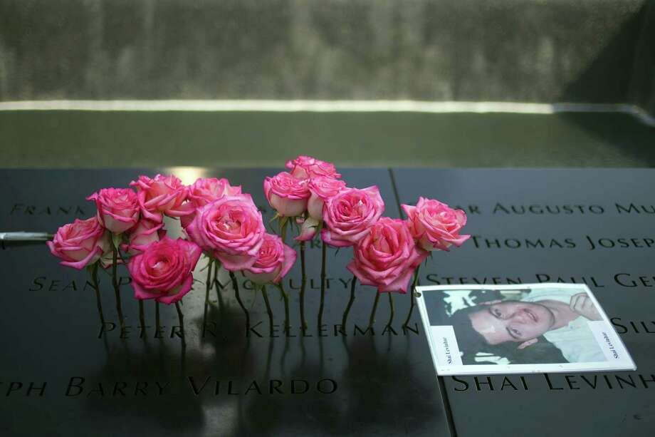 Roses are placed on the inscribed name of Peter Kellerman next to an image of Shai Levinhar along the North Pool during 9/11 Memorial ceremonies marking the 12th anniversary of the 9/11 attacks on the World Trade Center in New York on September 11, 2013. Photo: ADREES LATIF, AFP/Getty Images / AFP ImageForum