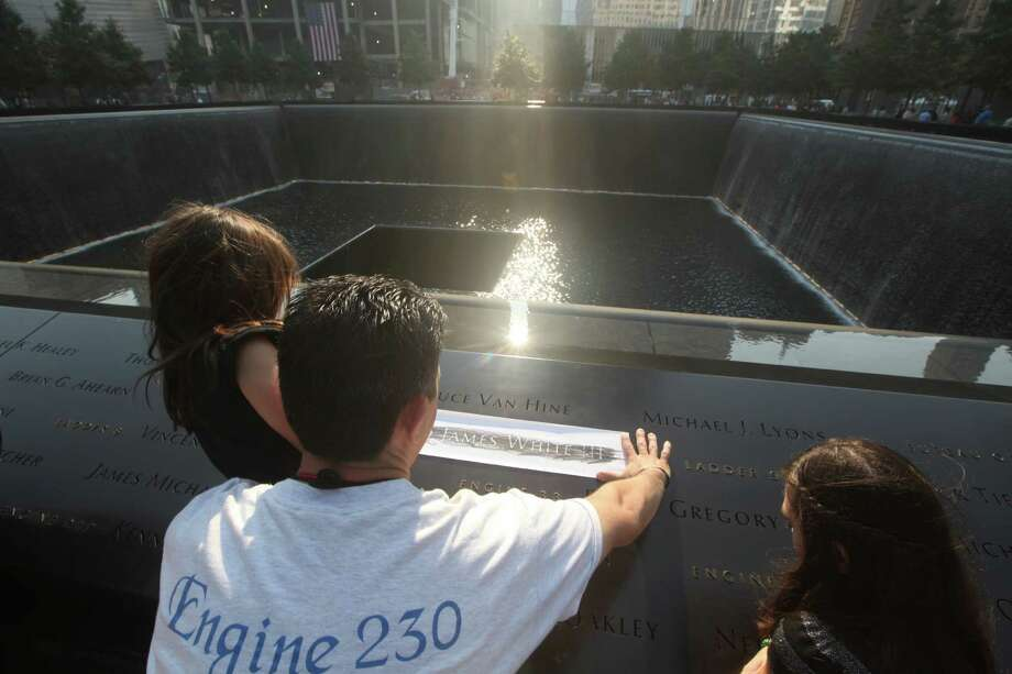 Steve Antoniou of Queens, brother-in-law of Edward James White III, a NYC firefighter killed on 911, holds his daughter Stella 6 as she and her sister Nikole 11 etch the name of their uncle. They are at the 9/11 Memorial during ceremonies marking the 12th anniversary of the 9/11 attacks on the World Trade Center in New York, September 11, 2013. Photo: CHRIS PEDOTA, Associated Press / THE RECORD Pool