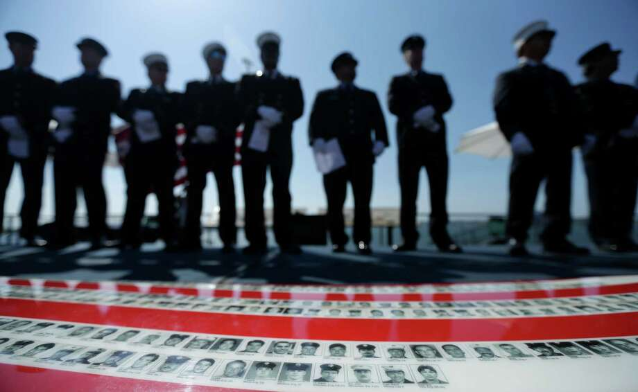 New York firefighters stand behind a surfboard, below, displaying the names and photos of firefighters killed during the Sept. 11, 2001 attacks,  during a Sept. 11 remembrance ceremony Wednesday, Sept. 11, 2013, on the flight deck of the USS Midway aircraft carrier in San Diego. About fifteen New York firefighters, many of whom responded to the World Trade Center on Sept. 11, 2001, were honored Wednesday in San Diego, as they took turns reading the names of fellow firefighters who lost their lives in the attacks. Photo: Gregory Bull, Associated Press / AP
