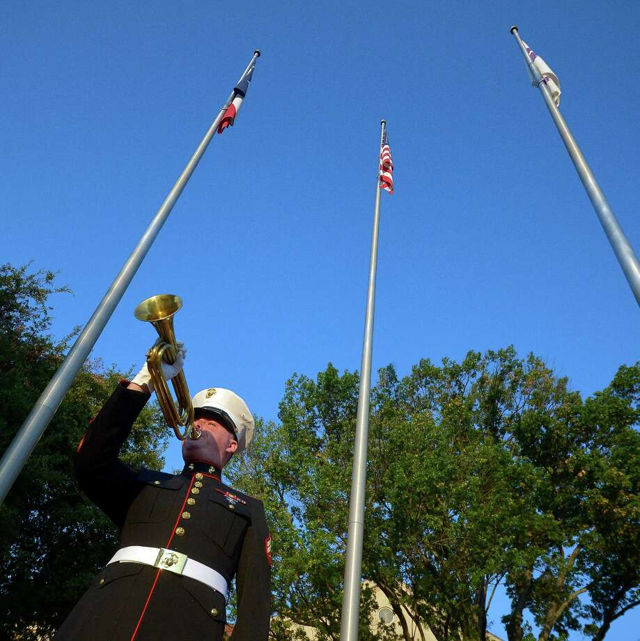 Marine veteran Andrew Lahey plays Taps at 8:03 a.m. at the flagpole on the TCU campus to honor the victims of 9/11 on Wednesday, Sept. 11, 2013 in Fort Worth.  Americans marked the 12th anniversary of the Sept. 11 terrorist attacks on Wednesday with the reading of the names, moments of silence and serene music that have become tradition.  At a morning ceremony on the 2-year-old memorial plaza at the site of the World Trade Center, relatives recited the names of the nearly 3,000 people who died when hijacked jets crashed into the twin towers and the Pentagon and near Shanksville, Pa. They also recognized the victims of the 1993 trade center bombing. Photo: Max Faulkner, Associated Press / The Fort Worth Star-Telegram