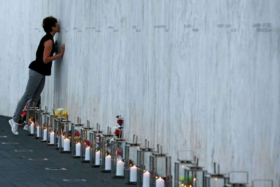 A visitor kisses an name on the wall  containing the 40 names of the crew and passengers of Flight 93 at the Flight 93 National Memorial during a candlelight remembrance on Tuesday, Sept. 10, 2013. Photo: Gene J. Puskar, Associated Press / AP