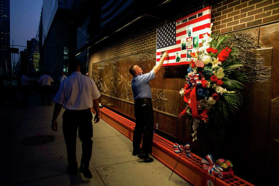 FDNY Firefighter Mike Bellantoni of New York prepares a memento at the Firefighter's Memorial adjacent to the World Trade Center Wednesday, Sept. 11, 2013 before the start of the official ceremonies at the 9/11 Memorial nearby. Photo: Craig Ruttle, Associated Press / FR61802 AP
