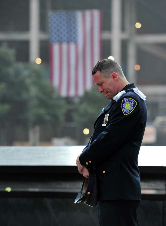 Daniel Henry, a Port Authority of New York/New Jersey police officer, pauses during a moment of silence at 9:01 a.m. at the south reflecting pool at the 9/11 Memorial on Wednesday, Sept. 11, 2013, during ceremonies marking the 12th anniversary of the 9/11 terrorist attacks in New York. Photo: Stan Honda, Associated Press / POOL AFP