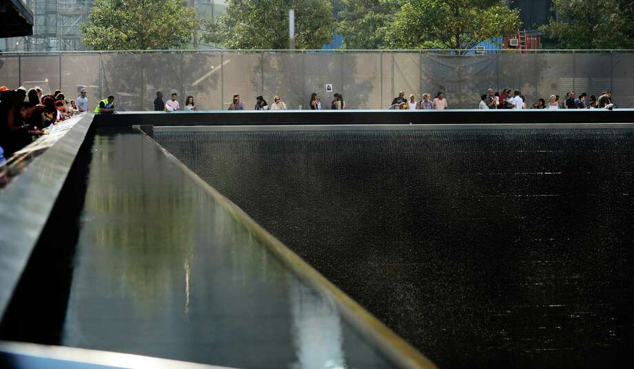 People stand along the 9/11 Memorial during ceremonies for the twelfth anniversary of the terrorist attacks on lower Manhattan at the World Trade Center site on September 11, 2013 in New York City. The nation is commemorating the anniversary of the 2001 attacks which resulted in the deaths of nearly 3,000 people after two hijacked planes crashed into the World Trade Center, one into the Pentagon in Arlington, Virginia and one crash landed in Shanksville, Pennsylvania. Following the attacks in New York, the former location of the Twin Towers has been turned into the National September 11 Memorial & Museum. Photo: Pool, Getty Images / 2013 Getty Images