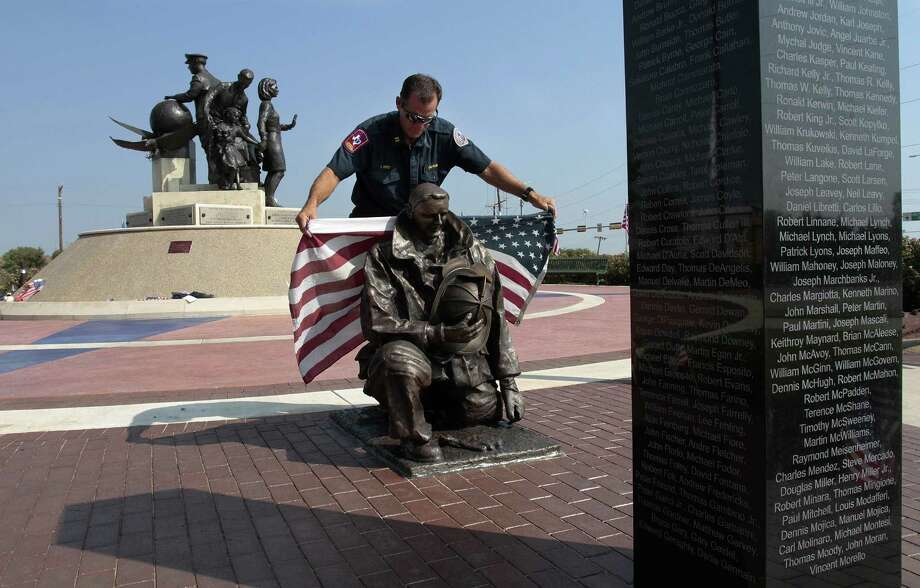 Grapevine Fire Department Captain/Assistant Fire Marshal Craig Reed replaces a flag around a statue of a firefighter after photographing the statue at The Flight Crew Memorial in Grapevine, Texas, Wednesday, September 11, 2013, on the 12th anniversary of the 9/11 attacks. Photo: Ian McVea, McClatchy-Tribune News Service / Fort Worth Star-Telegram
