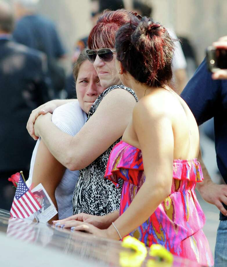 Mourners reacts at the 9/11 Memorial during ceremonies for the twelfth anniversary of the terrorist attacks on lower Manhattan at the World Trade Center site on September 11, 2013 in New York City. The nation is commemorating the anniversary of the 2001 attacks which resulted in the deaths of nearly 3,000 people after two hijacked planes crashed into the World Trade Center, one into the Pentagon in Arlington, Virginia and one crash landed in Shanksville, Pennsylvania. Following the attacks in New York, the former location of the Twin Towers has been turned into the National September 11 Memorial & Museum. Photo: Pool, Getty Images / 2013 Getty Images