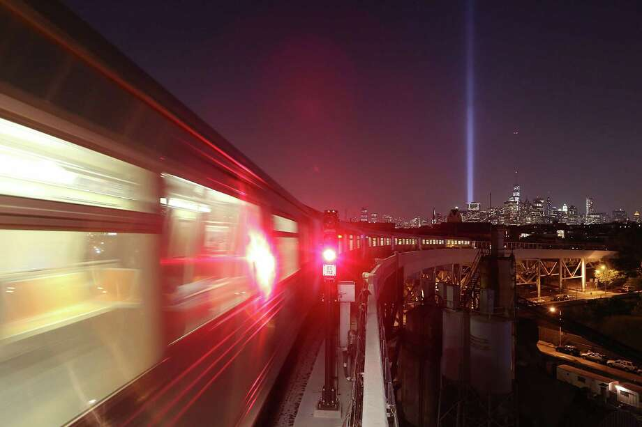 New York City's Tribute In Light shines in Manhattan (R) as a Brooklyn subway passes on the eve of the twelfth anniversary of the terrorist attacks at the World Trade Center on September 10, 2013 in New York City. New York City and the nation will commemorate the eleventh anniversary of the September 11, 2001 attacks, which resulted in the deaths of nearly 3,000 people after two hijacked planes crashed into the World Trade Center towers, one into the Pentagon in Arlington, Virginia and one into a field outside OF Shanksville, Pennsylvania. Photo: Mario Tama, Getty Images / 2013 Getty Images