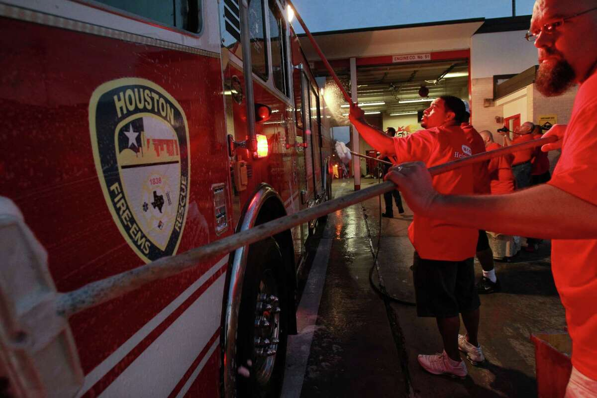 Stan Bailey, HEB employee, and other volunteers wash the ladder truck for firefighters at Houston Fire Station #51,