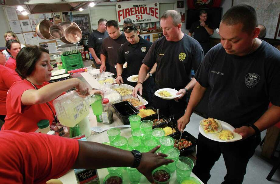 Firefighter Jesus Patricio leads a breakfast line as firefighters enjoy a breakfast cooked by HEB volunteers at Houston Fire Station #51. Photo: Mayra Beltran, Houston Chronicle / © 2013 Houston Chronicle