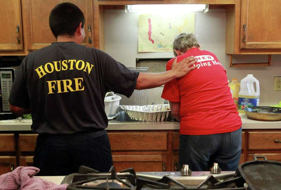A firefighter thanks an HEB volunteer after they cooked breakfast for the firefighters at Houston Fire Station #51. Photo: Mayra Beltran, Houston Chronicle / © 2013 Houston Chronicle