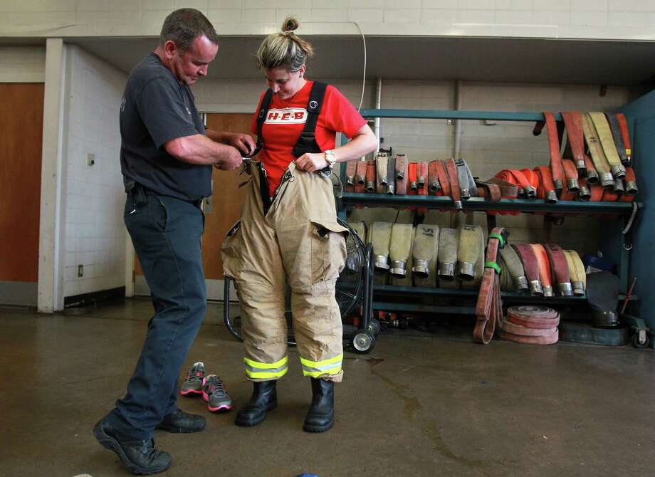 HFD Engineer Operator Kenny Helton helps HEB volunteer Kat Haag try on a fire protecting suit. Photo: Mayra Beltran, Houston Chronicle / © 2013 Houston Chronicle