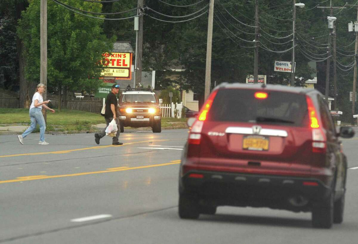 A couple crosses Central Avenue between Karner Road and Reber Street on Wednesday Sept. 11, 2013 in Colonie, N.Y. A look at the fatalities in the last dozen years showed six of the 16 happened near the small cluster of motels between Reber Street and Karner Road.(Michael P. Farrell/Times Union)