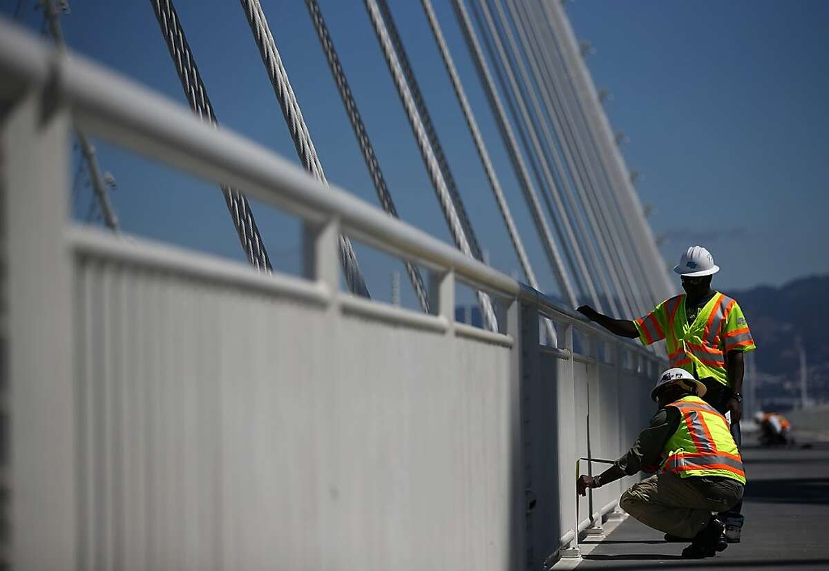 SAN FRANCISCO, CA - AUGUST 26: Workers make adjustements to a bike path next to the new Bay Bridge Self-Anchored Suspension (SAS) tower on August 26, 2013 in San Francisco, California. After nearly 12 years of construction and an estimated price tag of $6.4 billion, the new eastern span of the Bay Bridge is set to open on September 3. The bridge will be the world's tallest Self-Anchored Suspension (SAS) tower once completed. (Photo by Justin Sullivan/Getty Images)