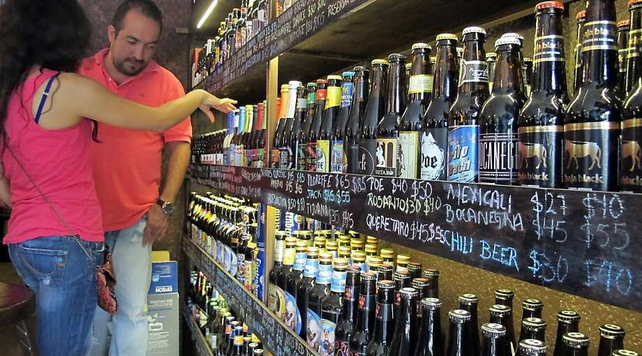 Shoppers look at a craft beer display at a Mexico City store. Small beer makers have struggled to break into a controlled market. Photo: Tim Johnson, McClatchy-Tribune News Service