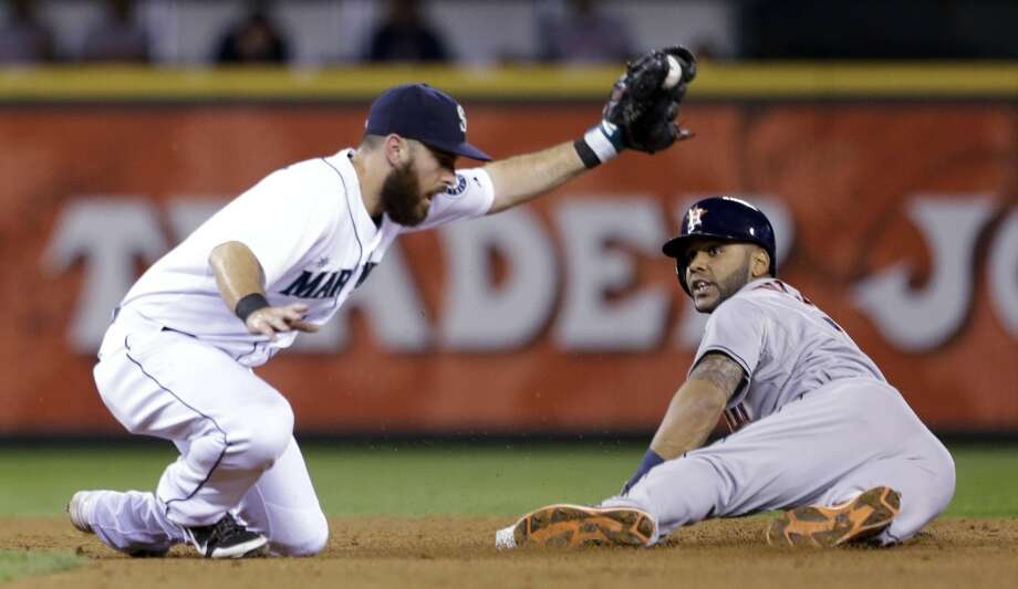 Mariners second baseman Dustin Ackley holds up the ball as Jonathan Villar looks for the call after sliding safely into second base for a stolen base. Photo: Elaine Thompson, Associated Press
