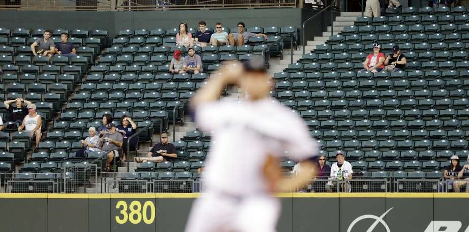 A handful of fans looks on as Mariners starting pitcher Brandon Maurer throws against the the Astros. Photo: Elaine Thompson, Associated Press