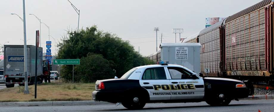 An 18-wheeler tractor trailer rig (left) is parked Thursday, Sept. 12, 2013, after a northbound Union Pacific freight train clipped the back of the truck at Fratt Road and Interstate 35. The minor accident happened about 8:10 a.m. and according to San Antonio police patrolman James Foster the eastbound truck could not clear the tracks because of heavy traffic backed up on the I-35 feeder road. Foster said there were no injuries, but that Walzem road would remain blocked by the train until the scene could be cleared. A train crashed into a truck at the same place on August 27, 2013. (John Davenport/Express-News) Photo: JOHN DAVENPORT, SAN ANTONIO EXPRESS-NEWS