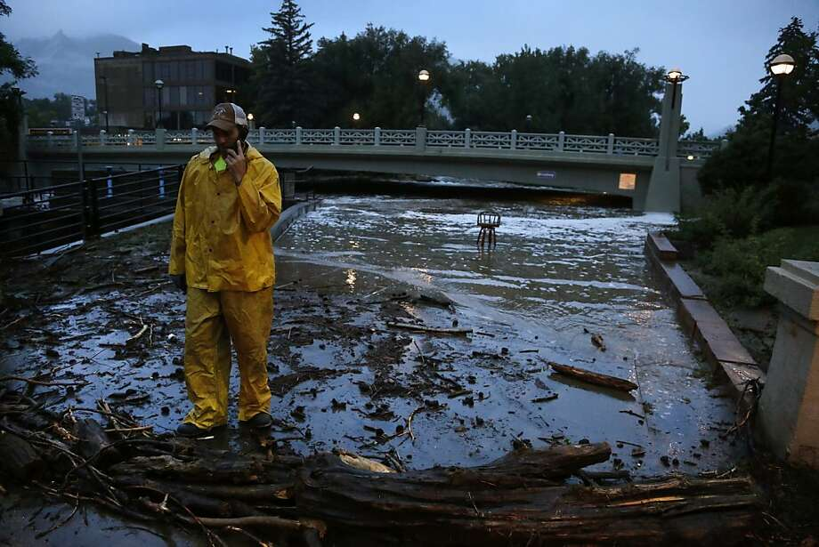 A city worker talks on his phone while surveying high water levels on Boulder Creek following overnight flash flooding in downtown Boulder, Colo., Thursday, Sept 12, 2013. Flash flooding in Colorado has left two people dead and the widespread high waters are keeping search and rescue teams from reaching stranded residents and motorists in Boulder and nearby mountain communities as heavy rains hammered northern Colorado. (AP Photo/Brennan Linsley) Photo: Brennan Linsley, Associated Press