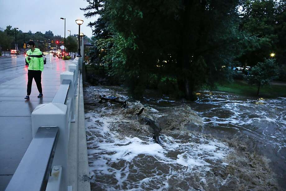 A man walks past dangerously high Boulder Creek following overnight flash flooding in downtown Boulder, Colo., Thursday, Sept 12, 2013. Flash flooding in Colorado has left two people dead and the widespread high waters are keeping search and rescue teams from reaching stranded residents and motorists in Boulder and nearby mountain communities as heavy rains hammered northern Colorado. (AP Photo/Brennan Linsley) Photo: Brennan Linsley, Associated Press