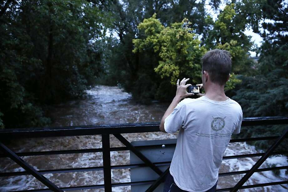 A man views dangerously high Boulder Creek following overnight flash flooding in downtown Boulder, Colo., Thursday, Sept 12, 2013. The flash flooding has left at least two people dead and the widespread high waters are keeping search and rescue teams from reaching stranded residents and motorists in Boulder and nearby mountain communities as heavy rains hammered northern Colorado. (AP Photo/Brennan Linsley) Photo: Brennan Linsley, Associated Press