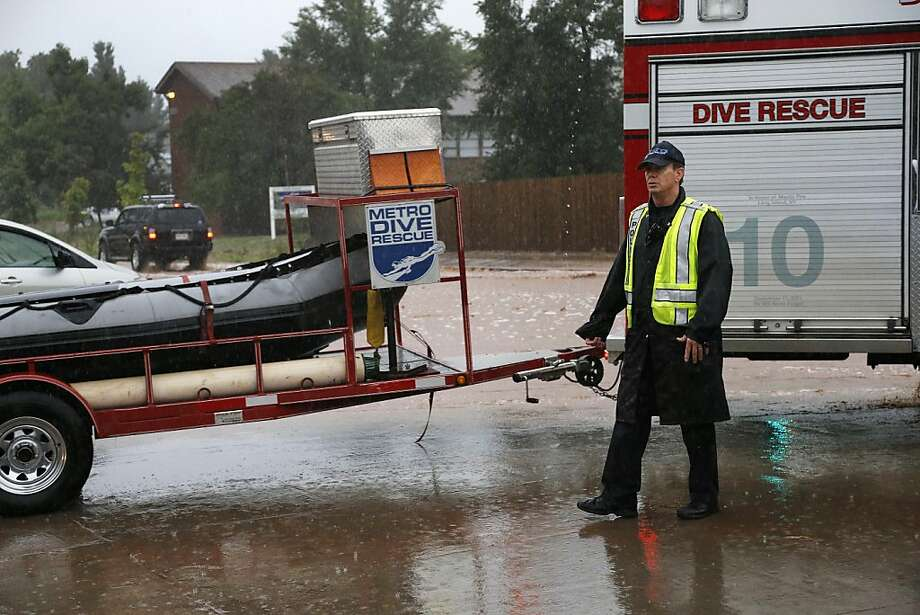 A police officer allows a special dive rescue team to pass on a closed road following overnight flash flooding in downtown Boulder, Colo., Thursday, Sept 12, 2013.  The widespread high waters are keeping search and rescue teams from reaching stranded residents and motorists in Boulder and nearby mountain communities as heavy rains hammered northern Colorado. (AP Photo/Brennan Linsley) Photo: Brennan Linsley, Associated Press