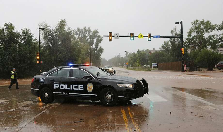 A police officer blocks a closed road following overnight flash flooding, Boulder, Colo., Thursday, Sept 12, 2013. The widespread high waters are keeping search and rescue teams from reaching stranded residents and motorists in Boulder and nearby mountain communities as heavy rains hammered northern Colorado. (AP Photo/Brennan Linsley) Photo: Brennan Linsley, Associated Press