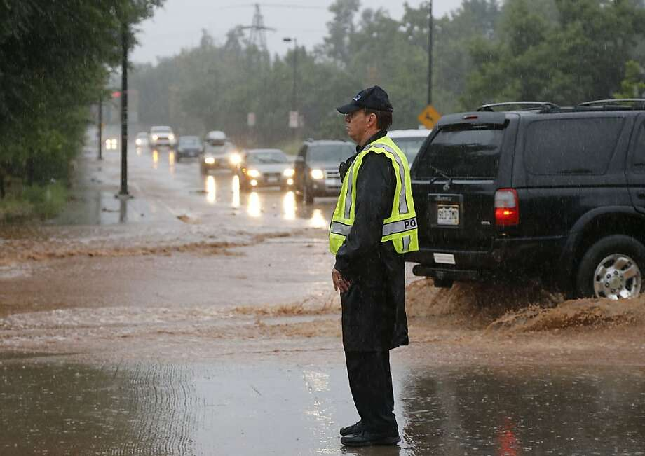 A police officer blocks traffic on a closed road following overnight flash flooding in the area, in Boulder, Colo., Thursday, Sept 12, 2013.  The widespread high waters are keeping search and rescue teams from reaching stranded residents and motorists in Boulder and nearby mountain communities as heavy rains hammered northern Colorado. (AP Photo/Brennan Linsley) Photo: Brennan Linsley, Associated Press