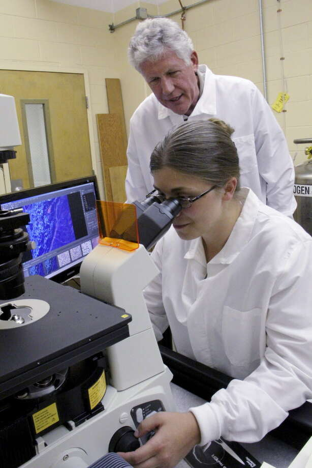 Sara Smith, of Petersburg, left, sits with Peter Schaefer, Depart Chair of Biology, Chemistry, and Physics, right, at Hudson Valley Community College, Troy, sits in the imaging lab on campus on Thursday, July 14, 2011. Smith was a student at HVCC and after receiving her Advanced Certificate in Biotechnology, and continues to work on a bio manufacturing project this summer.  Smith and Schaefer work on confocal microscope that was part of a federal grant given to the school. (Erin Colligan / Special To The Times Union) Photo: Erin Colligan / 00013932A
