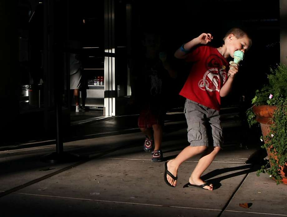 Riley Gates (right), 6, eats ice cream while running around a corner with Addison DeWolff, 5, outside of Cream in Walnut Creek. Photo: Leah Millis, The Chronicle