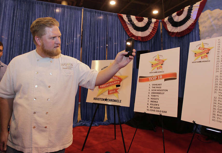Haven and Cove Cold Bar chef/co-Owner Randy Evans  photographs the list during the Alison Cook's Top 100 Restaurants, 2013 edition winner announcements at Reliant Center Sept. 11, 2013. Photo: James Nielsen, Houston Chronicle / © 2013  Houston Chronicle