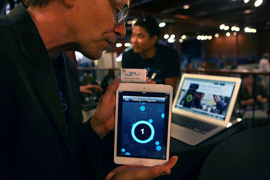 Charles Yim (background), CEO of Breathometer, demonstrates his company's device that allows people to measure their blood-alcohol levels by attaching it to a smartphone. Photo: Liz Hafalia, The Chronicle